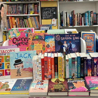 Collection of LGBTQ+ books at Child's Play for Pride Month