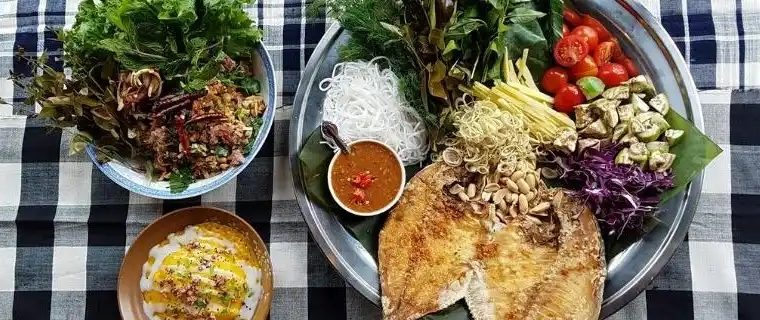 Plates of Thip Khao Laotian food on checkered tablecloth